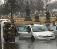Firefighters carry elderly women to safety from floodwaters
