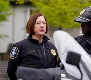 In this May 1, 2017 file photo, former Seattle Police Chief Kathleen O'Toole, left, talks with an officer before a march for worker and immigrant rights at a May Day event in Seattle. (AP Photo/Elaine Thompson, File)