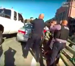 In this Thursday, Nov. 9, 2017 still file image from an officer's body camera video released by the Providence Police Department, officers converge on a truck driven into another vehicle by Joseph Santos on a highway on-ramp in downtown Providence, R.I. Police shot Santos dead, and injured passenger Christine Demers, who was hospitalized. (Providence Police Department via AP, File)