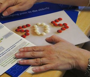 In this May 4, 2017 photo, Melissa Jones, a nurse educator with Alosa Health, explains educational materials on opioids and managing pain at a doctor's office in Elizabeth, Pa. Jones visits medical offices in western Pennsylvania to educate doctors about new opioid prescribing guidelines. (AP Photo/Carla K. Johnson)