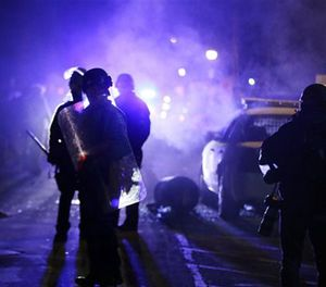 In this Nov. 25, 2014 file photo, police officers watch protesters as smoke fills the streets in Ferguson, Mo. (AP Image)