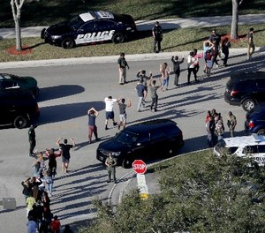 In this Feb. 14, 2018 file photo, students hold their hands in the air as they are evacuated by police from Marjory Stoneman Douglas High School in Parkland, Fla., after a shooter opened fire on the campus. (Mike Stocker/South Florida Sun-Sentinel via AP)