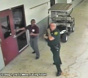 This Feb. 14, 2018 frame from security video provided by the Broward County Sheriff's Office shows deputy Scot Peterson, right, outside Marjory Stoneman Douglas High School in Parkland, Fla. The video released Thursday, March 15, shows Peterson going toward the high school building while a gunman massacred 17 students and staff members, but stayed outside with his handgun drawn. (Courtesy of the Broward County Sheriff's Office via AP)
