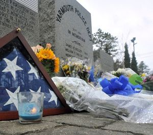 Rain wets the floral tribute to fallen officer Sean Gannon outside the Yarmouth Police Station on Friday, April 13, 2018. (Steve Heaslip /The Cape Cod Times via AP)