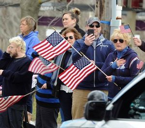 Well wishers line up outside the Doane Beal and Ames Funeral home on West Main Street in Hyannis, Mass., Tuesday, April 17, 2018, where the body of Yarmouth Police Officer Sean Gannon was transported by motorcade to South Yarmouth. (Ron Schloerb/The Cape Cod Times via AP)