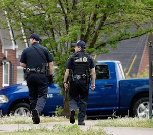 Nashville police officers search a neighborhood near a Waffle House restaurant Sunday, April 22, 2018, in Nashville, Tenn. At least four people died after a gunman opened fire at the restaurant early Sunday. (AP Photo/Mark Humphrey)