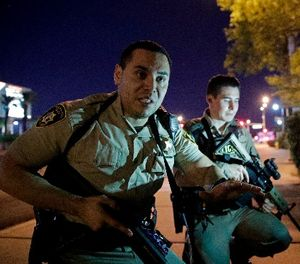 In this Oct. 1, 2017 file photo, police officers advise people to take cover near the scene of a shooting near the Mandalay Bay resort and casino on the Las Vegas Strip in Las Vegas. (AP Photo/John Locher, File)