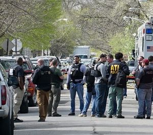 In this May 4, 2018 file photo Police from various agencies investigate the scene where a Bureau of Alcohol, Tobacco, Firearms and Explosives agent was shot, May 4, 2018, in Chicago. A law enforcement official says a suspect has been arrested in the shooting. (AP Photo/Teresa Crawford File)