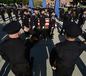 Officers with the Terre Haute Police Department and members of other agencies form a cordon to pay respect to fallen Terre Haute Police Officer Rob Pitts as his casket is carried on Tuesday, May 8, 2018, outside of Hulman Center in Terre Haute, Ind. (Joseph C. Garza/The Tribune-Star via AP)
