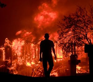 In this Oct. 9, 2017, file photo, Jim Stites watches part of his neighborhood burn in Fountaingrove, Calif. (Kent Porter/The Press Democrat via AP, File)