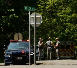 New York State Police block the entrance of Welch Road in Corning, N.Y., Monday, July 2, 2018, as they investigate the scene of a shooting near SUNY Corning Community College. A New York state trooper responding to a domestic call early Monday morning was killed along with a suspect, officials said. (AP Photo/Heather Ainsworth)
