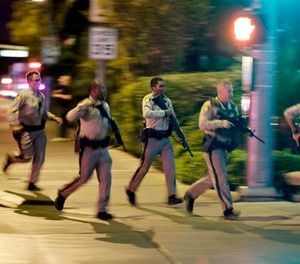 In this Oct. 1, 2017, file photo, police run toward the scene of a shooting near the Mandalay Bay resort and casino on the Las Vegas Strip in Las Vegas. (AP Photo/John Locher, File)