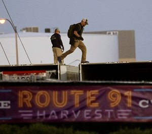 In this Oct. 3, 2017, file photo, FBI agents walk on the roof of boxes inside the concert grounds where a mass shooting occurred in Las Vegas. (AP Photo/John Locher, File)
