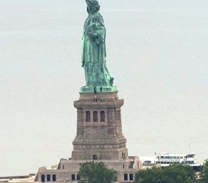 In this image taken from video, people climb on the pedestal of the Statue of Liberty in New York Harbor Wednesday, July 4, 2018. (AP Photo)
