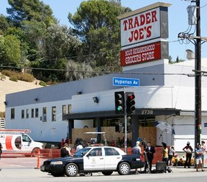 Police officers guard the entrance to the Trader Joe's Los Feliz store, as it remains closed for business, Sunday, July 22, 2018, in Los Angeles. (AP Photo/Damian Dovarganes)
