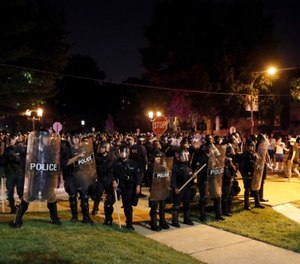 In this Sept. 15, 2017 file photo, police line up as protesters gather, in St. Louis, after a judge found Jason Stockley, a white former St. Louis police officer, not guilty of first-degree murder in the death of Anthony Lamar Smith, a black man, who was fatally shot following a high-speed chase in 2011. (AP Photo/Jeff Roberson, File)