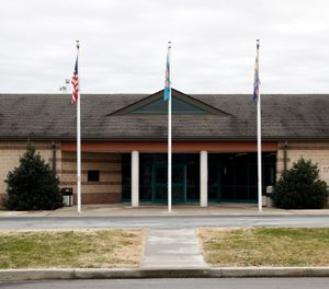 This Dec. 22, 2017, file photo shows the front entrance of the James T. Vaughn Correctional Center in Smyrna, Del. Delaware taxpayers have shelled out more than $360,000 in legal defense costs for 18 prisoners charged in a deadly prison riot last year - and the bills will continue to pile up as the trials get under way. (AP Photo/Patrick Semansky, File)