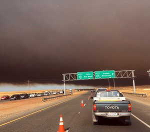 Smoke from the Camp Fire, burning in the Feather River Canyon near Paradise, Calif., darkens the sky as seen from Highway 99 near Marysville, Calif., Thursday, Nov. 8, 2018. (AP Photo/Don Thompson)