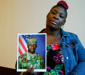 "April Pipkins holds a photograph of her deceased son, Emantic ""EJ"" Bradford Jr., during an interview in Birmingham, Ala. A police officer will not face charges for killing Bradford Jr, a man he mistook for the gunman in an Alabama mall shooting on Thanksgiving night. (AP Photo/Jay Reeves, File)"
