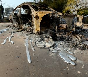 This Nov. 10, 2018, file photo shows molten aluminum that flowed from a car that burned in front of one of at least 20 homes destroyed just on Windermere Drive in the Point Dume area of Malibu, Calif., (AP Photo/Reed Saxon, File)