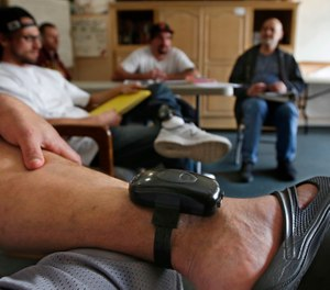 In this photo taken Wednesday, Feb. 20, 2019, a GPS bracelet is seen on the ankle of an inmate attending a discussion about living in sobriety at the Male Community Re-entry Program in Oroville, Calif. (AP Photo/Rich Pedroncelli)