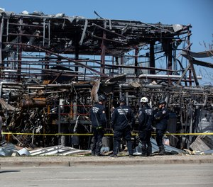 Debris can be seen as emergency personnel and others search and clear the scene of an explosion and fire at AB Specialty Silicones chemical plant Saturday, May 4, 2019, in Waukegan, Ill. An explosion and fire at an Illinois silicone factory was believed to have killed three people, authorities said Saturday, as they recovered the body of one victim while suspending the search for the other two. (Erin Hooley/Chicago Tribune via AP)