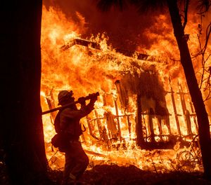 In this Nov. 9, 2018 file photo, firefighter Jose Corona sprays water as flames from the Camp Fire consume a home in Magalia, Calif. Federal officials say an effort to develop a better fire shelter following the deaths of 19 wildland firefighters in Arizona six years ago has failed. (AP Photo/Noah Berger, File)