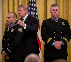 President Donald Trump awards Fire Captain Dustin Moore, right, and Firefighter Paramedic Andrew Freisner, left, of the Lenexa Fire Department, Kansas, the Public Safety Officer Medal of Valor at a ceremony in the East Room of the White House in Washington, Wednesday, May 22, 2019.(AP Photo/Andrew Harnik)