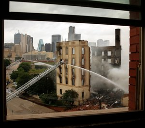 Dallas firefighters pour water on the destroyed historic Ambassador hotel just south of downtown Dallas, Tuesday, May 28, 2019. Over 100 firefighters responded to the four-alarm fire. (Tom Fox/The Dallas Morning News via AP)