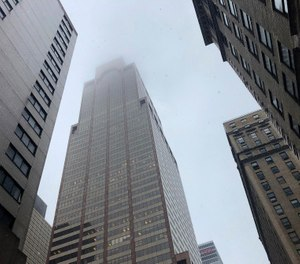 Mist and smoke cover the top of a building near 51st Street and 7th Avenue Monday, June 10, 2019, in New York, where a helicopter was reported to have crash landed on top of the roof of a building in midtown Manhattan. (AP Photo/Mark Lennihan)