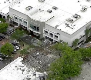 This image taken from video provided by WPLG shows debris covering the parking lot of a shopping center after an explosion on in Plantation, Fla. The explosion happened Saturday morning at the shopping center, west of Fort Lauderdale in Broward County. The blast sent large pieces of debris about 100 yards (about 91 meters) across the street. (WPLG via AP)