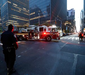 Fire trucks respond during a widespread power outage in New York City. (AP Photo/Michael Owens)