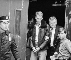 Bernhard Goetz, escorted by detectives, leaves New York Police headquarters, Jan. 3, 1984, after his return from Concord, N.H., where he turned himself in and admitted to shooting four youths on a New York subway train in December. (AP Photo)