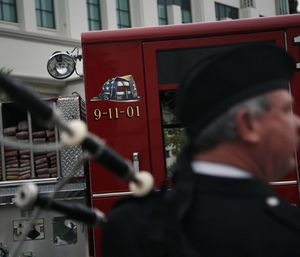 Bagpipe player Glen Thompson looks on as police and firefighters gather to remember the moment the first plane struck the World Trade Center. (Photo/AP)