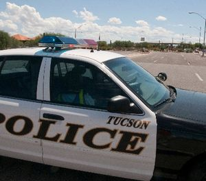A police car blocks an entrance to Davis-Monthan Air Force Base in Tucson, Ariz., Friday, Sept. 16, 2011. (AP Photo/Gary M. Williams)