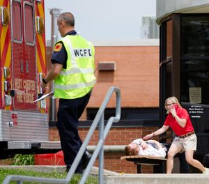 Volunteers participating in a training exercise for an active shooter simulate exiting the main entrance of Hopewell Elementary School with injuries Wednesday, May 25, 2016, in West Chester, Ohio. (AP Photo/John Minchillo)