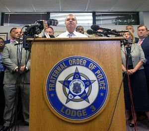 Gene Ryan, center, president of the Baltimore Fraternal Order of Police, speaks during a news conference in Baltimore, Wednesday, July 27, 2016. (AP Photo/Steve Ruark)
