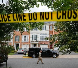 A law enforcement officer walks on the street outside the home of Nicholas Young, a Washington Metro Transit Officer, Wednesday, Aug. 3, 2016, in Fairfax, Va. (AP Photo/Pablo Martinez Monsivais)