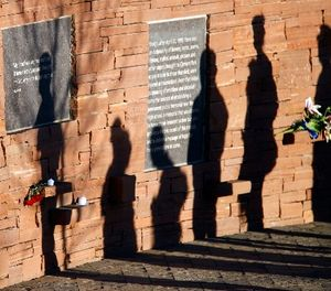 In this April 20, 2009, file photo, shadows are cast on the wall of the Columbine Memorial by visitors after a memorial service to mark the 10th anniversary of the massacre at Columbine High School in the southwest Denver suburb of Littleton, Colo. (AP Photo/Jack Dempsey, File)