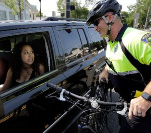 In this July 20, 2016 photo, police officer Matthew Monteiro speaks to a motorist about texting while driving while patrolling on his bicycle in West Bridgewater, Mass. (AP Photo/Steven Senne)
