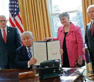 President Donald Trump holds up newly signed executive order aimed at preventing violence against Federal, State, Tribal and local law enforcement officers, Thursday, Feb. 9, 2017, in the Oval Office of the White House in Washington. (AP Photo/Pablo Martinez Monsivais)