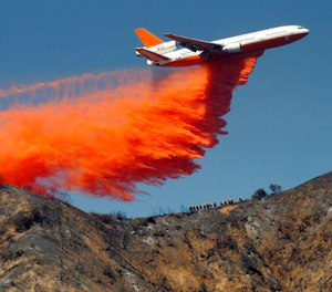 In this Tuesday, Sept. 24, 2013 file photo, a DC-10 airplane tanker drops fire retardant to battle a wildfire in the San Gabriel Mountains in Azusa, Calif. (AP Photo/Nick Ut)