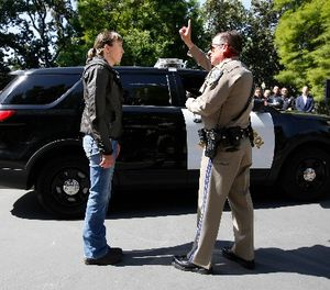 California Highway Patrol Officer Gary Martens, right, has CHP Sgt. Jaimi Kenyon, follow his finger during a demonstration of how drivers, suspected of impaired driving, are currently tested, Wednesday, May 10, 2017, in Sacramento, Calif. (AP Photo/Rich Pedroncelli)