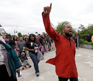 Andre Taylor, whose brother Che Taylor was killed by police in 2016, yells as he leads others to a vigil outside where a pregnant mother was shot and killed Sunday by police, Tuesday, June 20, 2017 in Seattle. (AP Photo/Elaine Thompson)