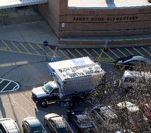 n this Dec. 14, 2012 aerial file photo, officials stand outside of Sandy Hook Elementary School in Newtown, Conn. (AP Photo/Julio Cortez)