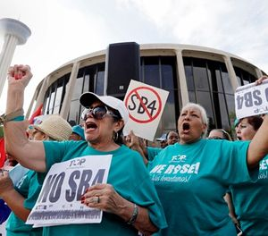 In this June 26, 2017, file photo, Lydia Balderas, left, and Merced Leyua, right, join others as they protest against a new sanctuary cities bill outside the federal courthouse in San Antonio. (AP Photo/Eric Gay, File)