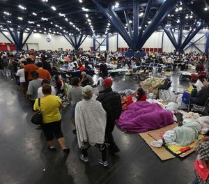 People line up for food as others rest at the George R. Brown Convention Center that has been set up as a shelter for evacuees escaping the floodwaters from Tropical Storm Harvey in Houston, Texas, Tuesday, Aug. 29, 2017. (AP Photo/LM Otero)