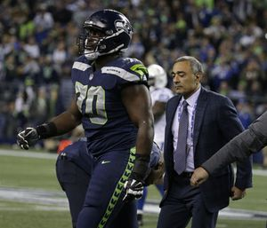 Seattle Seahawks offensive tackle Rees Odhiambo leaves the field with an injury in the second half of an NFL football game. (Photo/AP)