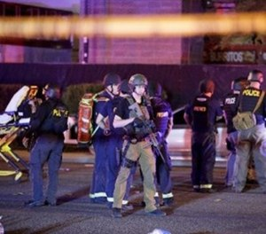 In this Oct. 2, 2017, file photo, police officers and medical personnel stand at the scene of the shooting near the Mandalay Bay resort and casino on the Las Vegas Strip in Las Vegas. (AP Photo/John Locher, File)