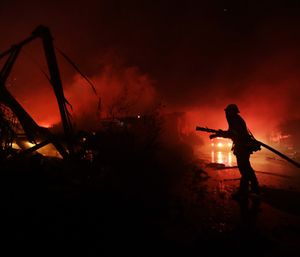Fire crews work among destroyed homes at the Rancho Monserate Country Club community. (Photo/AP)